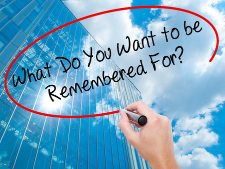 remembered: Man Hand writing What Do You Want to be Remembered For? with black marker on visual screen. Business, technology, internet concept. Modern business skyscrapers background. Stock Photo