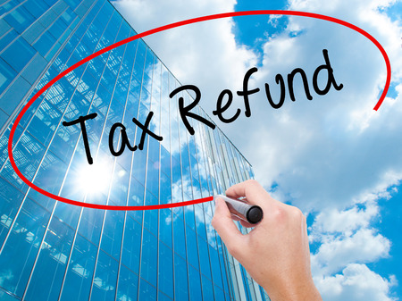 Man Hand writing Tax Refund with black marker on visual screen. Business, technology, internet concept. Modern business skyscrapers background. Stock Photo