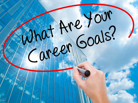 Man Hand writing What Are Your Career Goals? with black marker on visual screen. Business, technology, internet concept. Modern business skyscrapers background. Stock Photo