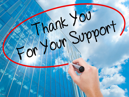 Man Hand writing Thank you For Your Support  with black marker on visual screen.  Business, technology, internet concept. Modern business skyscrapers background. Stock Photo Stock Photo