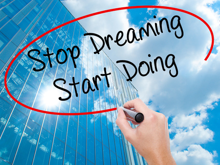Man Hand writing Stop Dreaming Start Doing  with black marker on visual screen.  Business, technology, internet concept. Modern business skyscrapers background. Stock Photo