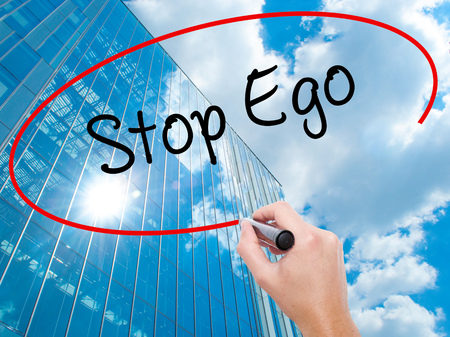 Man Hand writing  Stop Ego with black marker on visual screen.  Business, technology, internet concept. Modern business skyscrapers background. Stock Photo Stock Photo