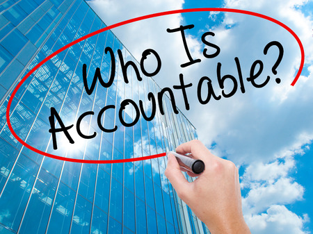 justify: Man Hand writing Who Is Accountable? with black marker on visual screen. Business, technology, internet concept. Modern business skyscrapers background. Stock Image