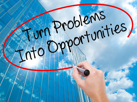 Man Hand writing Turn Problems into Opportunities with black marker on visual screen.  Business, technology, internet concept. Modern business skyscrapers background. Stock Photo