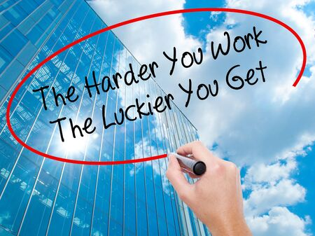 a placard: Man Hand writing The Harder You Work The Luckier You Get  with black marker on visual screen. Business, technology, internet concept. Stock Photo