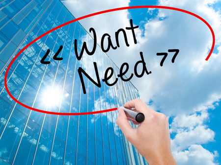 Man Hand writing Want - Need  with black marker on visual screen.  Business, technology, internet concept. Modern business skyscrapers background. Stock Photo