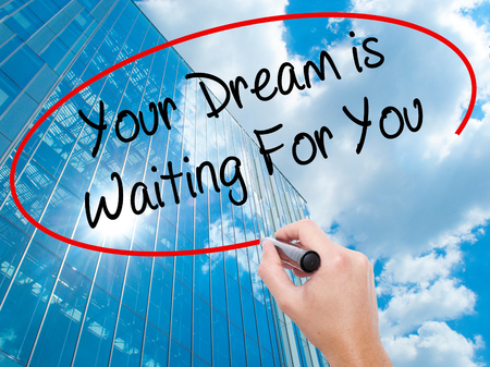 Man Hand writing Your Dream is Waiting For You with black marker on visual screen.  Business, technology, internet concept. Modern business skyscrapers background. Stock Photo Stock Photo