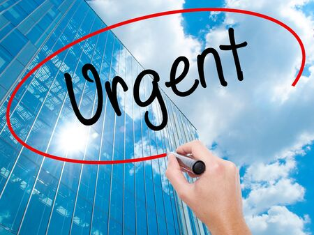 Man Hand writing Urgent  with black marker on visual screen.  Business, technology, internet concept. Stock  Photo