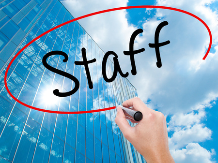 Man Hand writing  Staff with black marker on visual screen.  Business, technology, internet concept. Modern business skyscrapers background. Stock Photo