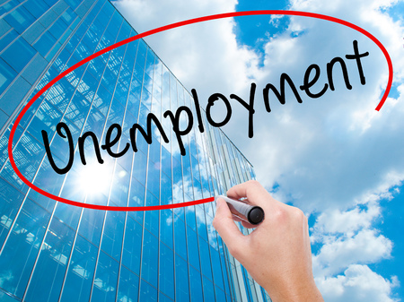 Man Hand writing  Unemployment with black marker on visual screen. Business, technology, internet concept. Modern business skyscrapers background. Stock Photo