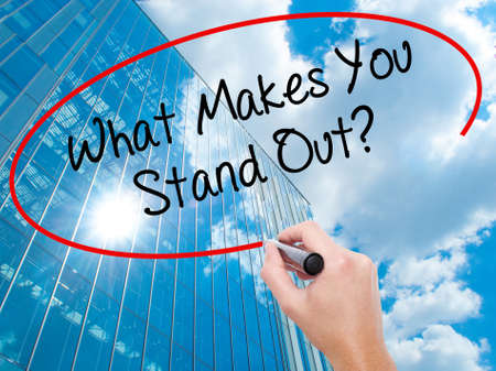Man Hand writing What Makes You Stand Out? with black marker on visual screen.  Business, technology, internet concept. Modern business skyscrapers background. Stock Photo