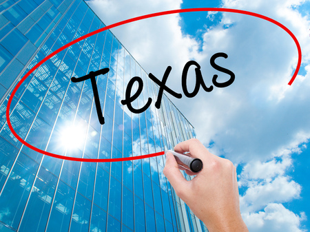 Man Hand writing Texas  with black marker on visual screen. Business, technology, internet concept.