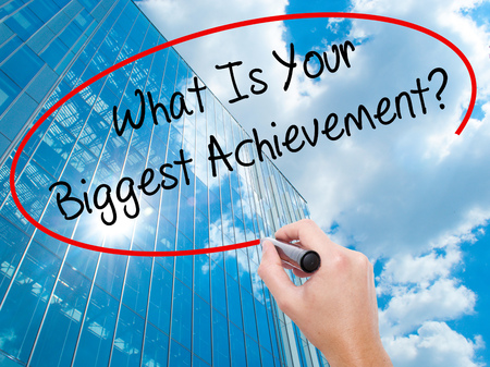 exceeding: Man Hand writing What Is Your Biggest Achievement? with black marker on visual screen.  Business, technology, internet concept. Modern business skyscrapers background. Stock Photo