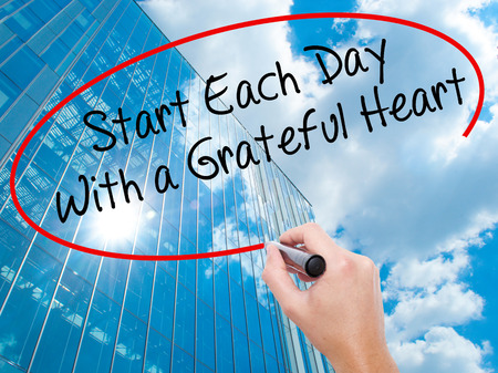 Man Hand writing Start Each Day With a Grateful Heart with black marker on visual screen. Business, technology, internet concept. Modern business skyscrapers background. Stock Photo Stock Photo