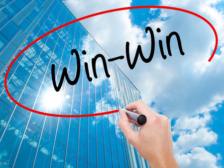 Man Hand writing Win-Win  with black marker on visual screen. Business, technology, internet concept. Modern business skyscrapers background. Stock Photo