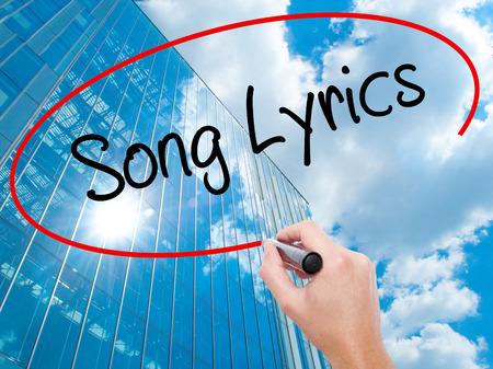 music lyrics: Escritura de la mano del hombre de canciónes con marcador negro en la pantalla visual. Negocios, la tecnología, el concepto de internet. Fondo moderno de los rascacielos de negocios. Foto de stock