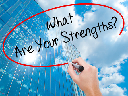 firmness: Man Hand writing What Are Your Strengths? with black marker on visual screen. Business, technology, internet concept. Modern business skyscrapers background. Stock Photo Stock Photo