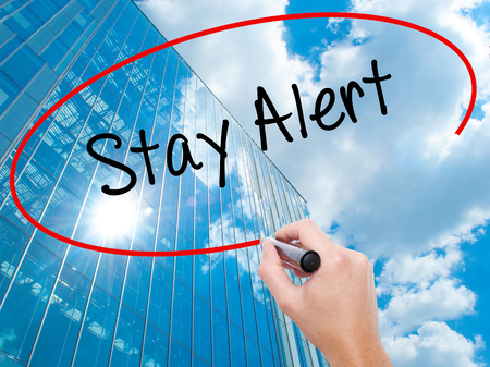 Man Hand writing Stay Alert with black marker on visual screen. Business, technology, internet concept. Modern business skyscrapers background. Stock Photo Stock Photo