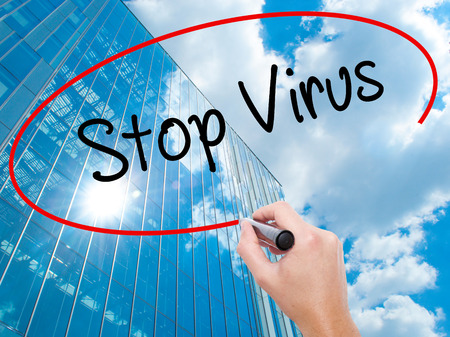 Man Hand writing Stop Virus with black marker on visual screen. Business, technology, internet concept. Modern business skyscrapers background. Stock Photo Stock Photo