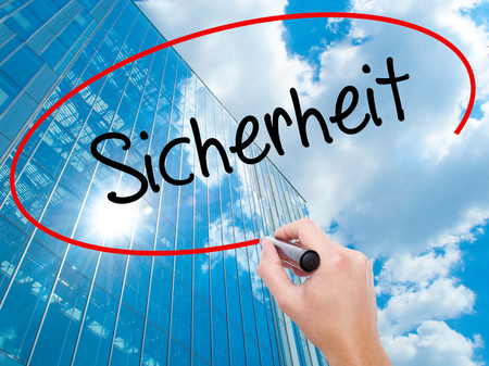 Man Hand writing Sicherheit (Safety in German) with black marker on visual screen. Business,  internet concept. Modern business skyscrapers background. Stock Photo