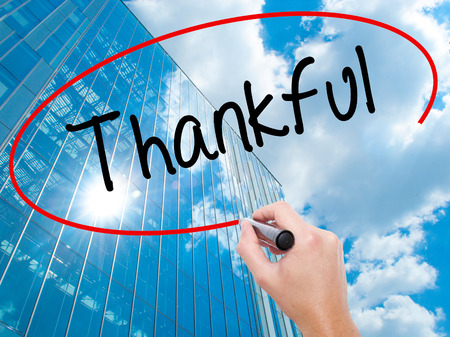 obliged: Man Hand writing Thankful  with black marker on visual screen.  Business, technology, internet concept. Modern business skyscrapers background. Stock Photo