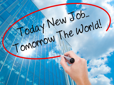 Man Hand writing Today New Job...Tomorrow The World! with black marker on visual screen.  Business, technology, internet concept. Modern business skyscrapers background. Stock Photo