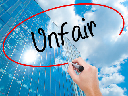 Man Hand writing Unfair with black marker on visual screen.  Business, technology, internet concept. Modern business skyscrapers background. Stock Photo