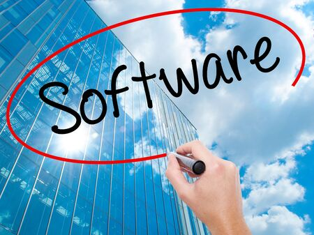 Man Hand writing Software  with black marker on visual screen.  Business, technology, internet concept. Modern business skyscrapers background. Stock Photo