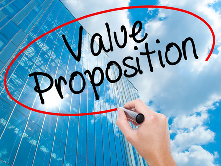 Man Hand writing Value Proposition with black marker on visual screen. Business, technology, internet concept. Modern business skyscrapers background. Stock Photo Stock Photo