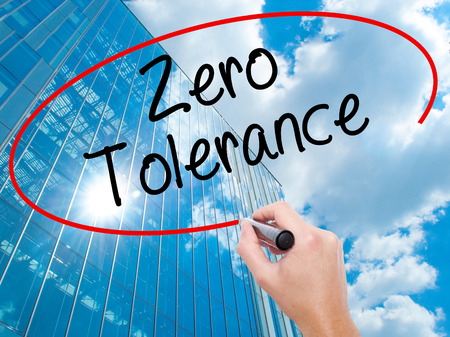 Man Hand writing Zero Tolerance with black marker on visual screen.  Business, technology, internet concept. Modern business skyscrapers background. Stock Photo