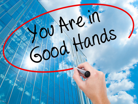 Man Hand writing You Are in Good Hands with black marker on visual screen. Business, technology, internet concept. Modern business skyscrapers background. Stock Photo