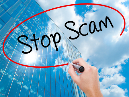 Man Hand writing Stop Scam with black marker on visual screen.  Business, technology, internet concept. Modern business skyscrapers background. Stock Photo