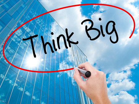 Man Hand writing Think Big with black marker on visual screen. Business, technology, internet concept. Modern business skyscrapers background. Stock Photo Stock Photo
