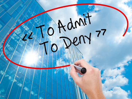 denying: Man Hand writing To Admit - To Deny with black marker on visual screen.  Business, technology, internet concept. Modern business skyscrapers background. Stock Photo