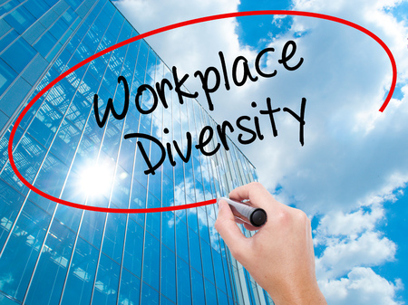 competitividad: Man Hand writing Workplace Diversity  with black marker on visual screen.  Business, technology, internet concept. Modern business skyscrapers background. Stock Photo
