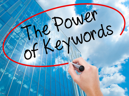 keyword research: Man Hand writing The Power of Keywords with black marker on visual screen. Business, technology, internet concept. Modern business skyscrapers background. Stock Photo