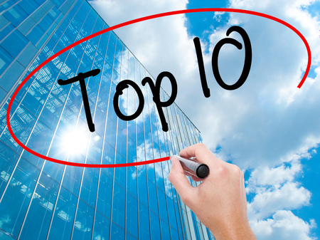 Man Hand writing Top 10 with black marker on visual screen. Business, technology, internet concept. Modern business skyscrapers background. Stock Photo