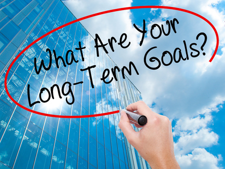Man Hand writing What Are Your Long-Term Goals? with black marker on visual screen. Business, technology, internet concept. Modern business skyscrapers background. Stock Photo