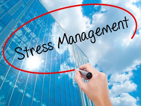 stressing: Man Hand writing Stress Management with black marker on visual screen. Business, technology, internet concept. Modern business skyscrapers background. Stock Photo