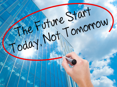 important date: Man Hand writing The Future Start Today, Not Tomorrow with black marker on visual screen.  Business, technology, internet concept. Modern business skyscrapers background. Stock Photo