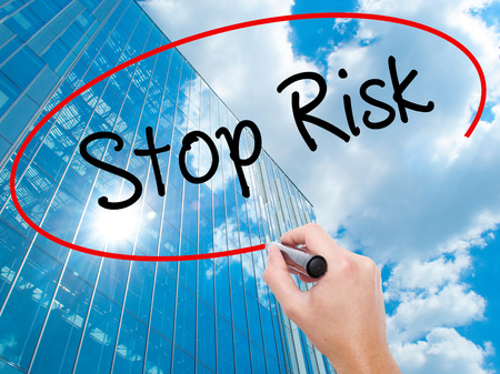 Man Hand writing Stop Risk with black marker on visual screen.  Business, technology, internet concept. Modern business skyscrapers background. Stock Photo