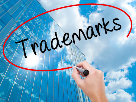 Man Hand writing Trademarks  with black marker on visual screen.  Business, technology, internet concept. Modern business skyscrapers background. Stock Photo Stock Photo
