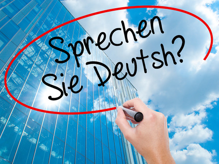 Man Hand writing Do You Speak German? (in German) with black marker on visual screen. Business, technology, internet concept. Modern business skyscrapers background. Stock Photo Stock Photo