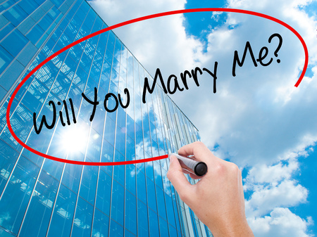 Man Hand writing Will You Marry Me? with black marker on visual screen.  Business, technology, internet concept. Modern business skyscrapers background. Stock Photo