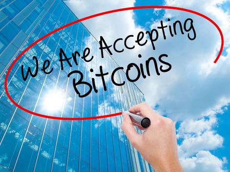 Man Hand writing We Are Accepting Bitcoins with black marker on visual screen. Business, technology, internet concept. Modern business skyscrapers background. Stock Photo