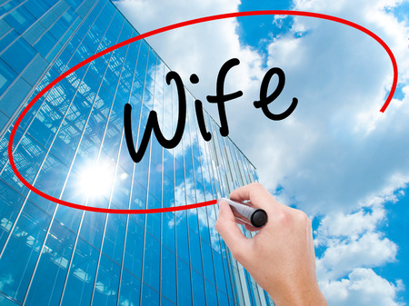 Man Hand writing Wife with black marker on visual screen.  Business, technology, internet concept. Modern business skyscrapers background. Stock Photo