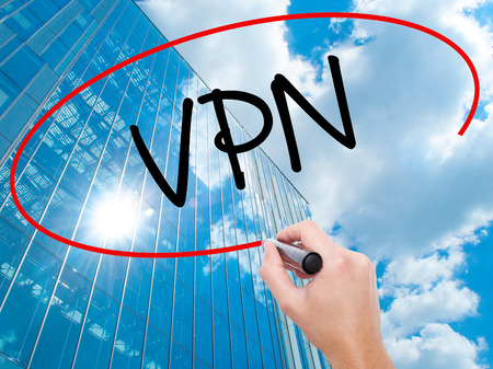 Man Hand writing VPN (Virtual Private Network) with black marker on visual screen.  Business, technology, internet concept. Modern business skyscrapers background. Stock Photo Stock Photo