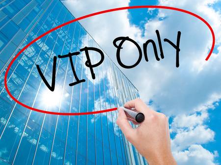 Man Hand writing VIP Only   with black marker on visual screen.  Business, technology, internet concept. Modern business skyscrapers background. Stock Photo