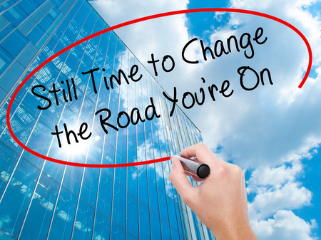 Man Hand writing Still Time to Change the Road Youre On with black marker on visual screen. Business, technology, internet concept. Modern business skyscrapers background. Stock Photo