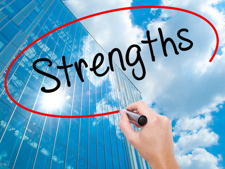 Man Hand writing Strengths with black marker on visual screen.  Business, technology, internet concept. Modern business skyscrapers background. Stock Photo